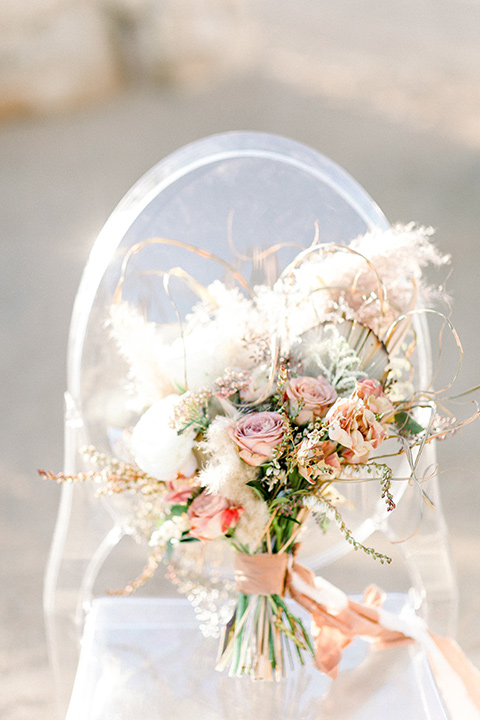 clear acrylic chairs with bridal bouquet on it with white and pink flowers
