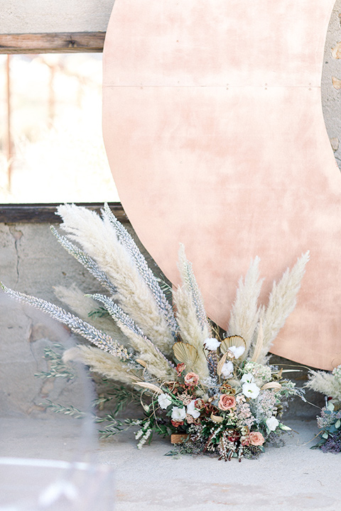 Rose gold moon ceremony décor and floral arrangements with pampas grass