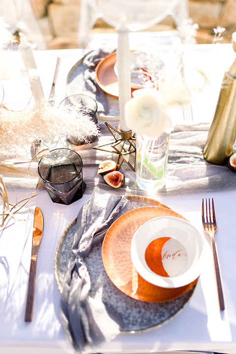 purple and silver table linens with tall white and gold candles with terracotta colored flatware