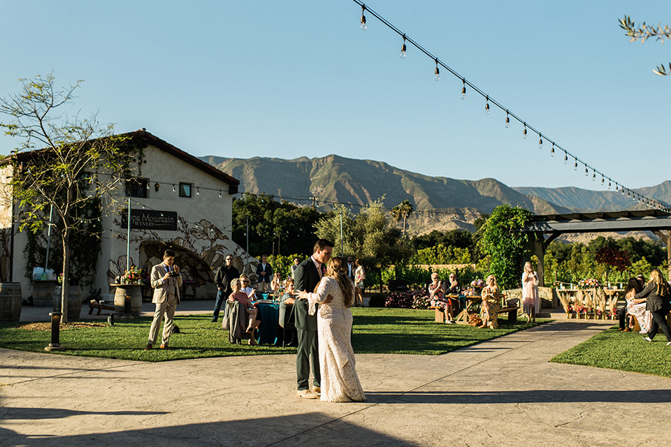 Topa-Winery-Wedding-bride-and-groom-first-dance-bride-in-a-bohemian-lace-gown-with-long-flowing-sleeves-groom-in-a-green-suit-with-a-tan-long-tie
