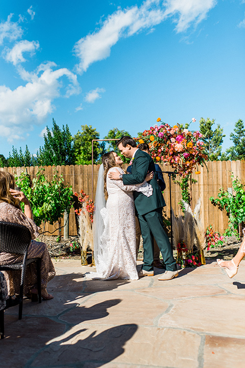 Topa-Winery-Wedding-bride-and-groom-first-kiss-bride-in-a-bohemian-gown-with-lace-detailing-and-flutter-sleeves-groom-in-a-green-suit-with-a-tan-tie-and-shoes