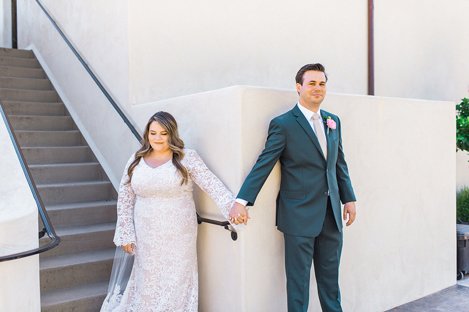 Topa-Winery-Wedding-bride-and-groom-first-look-bride-in-a-bohemian-lace-gown-with-long-flowing-sleeves-groom-in-a-green-suit-with-a-tan-long-tie