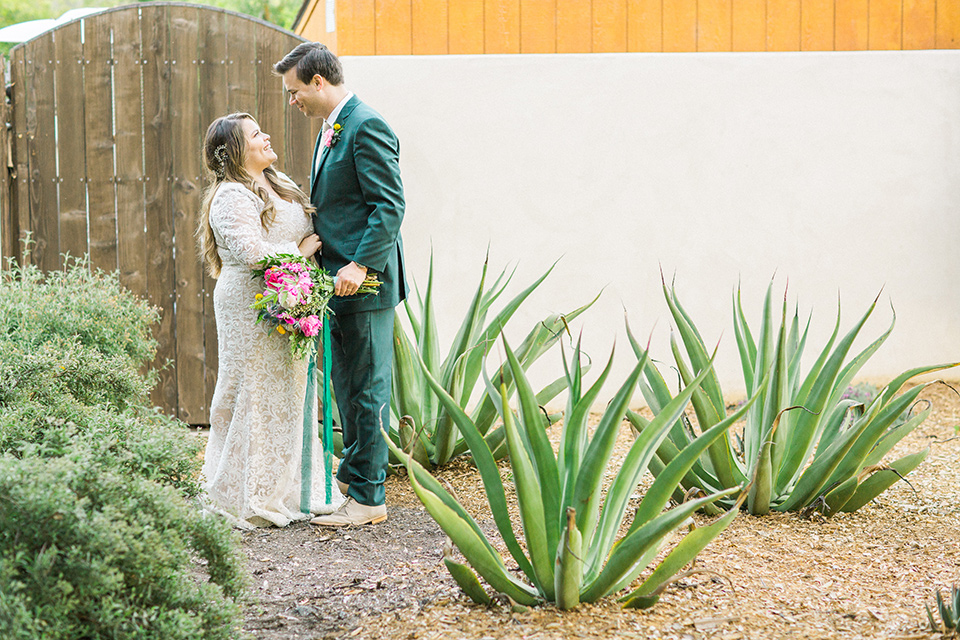 Topa-Winery-Wedding-bride-and-groom-in-venue-garden-bride-in-a-bohemian-lace-gown-with-long-flowing-sleeves-groom-in-a-green-suit-with-a-tan-long-tie