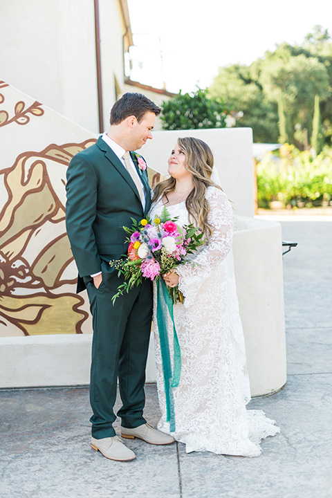 Topa-Winery-Wedding-bride-and-groom-looking-at-each-other-bride-in-a-bohemian-gown-with-lace-detailing-and-flutter-sleeves-groom-in-a-green-suit-with-a-tan-tie-and-shoes