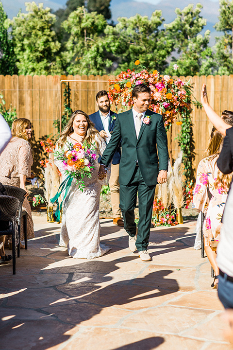 Topa-Winery-Wedding-bride-and-groom-walk-down-aisle-bride-in-a-lace-bohemian-style-gown-with-flutter-sleeves-groom-in-a-green-suit-with-a-tan-long-tie-with-brown-shoes