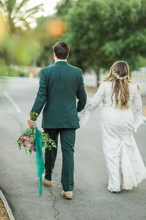 Topa-Winery-Wedding-bride-and-groom-walking-away-from-camera-bride-in-a-lace-bohemian-style-gown-with-flutter-sleeves-groom-in-a-green-suit-with-a-tan-long-tie-with-brown-shoes