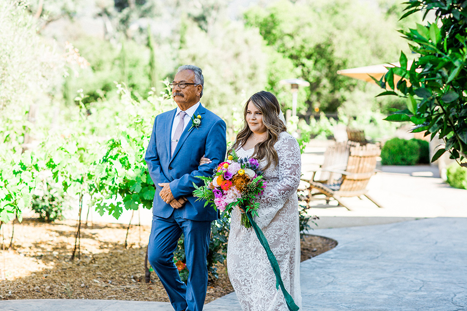 Topa-Winery-Wedding-bride-walking-down-aisle-bride-in-a-bohemian-lace-gown-with-long-flowing-sleeves-father-in-a-light-blue-suit