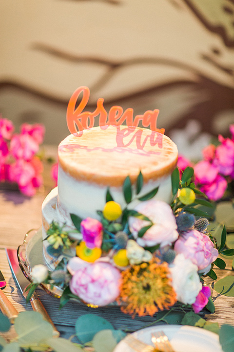 Topa-Winery-Wedding-cake-with-white-fondant-and-gold-trim-with-bright-florals-on-it