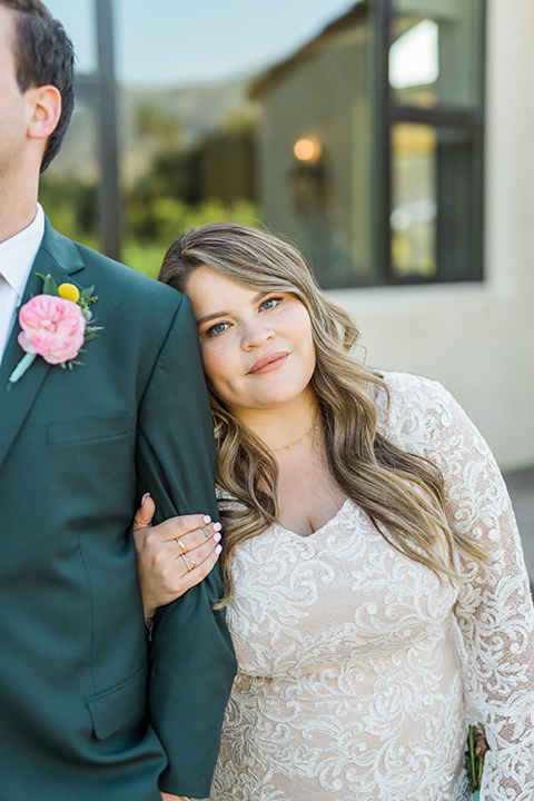 Topa-Winery-Wedding-close-up-on-couple-bride-in-a-lace-bohemian-style-gown-with-flutter-sleeves-groom-in-a-green-suit-with-a-tan-long-tie-with-brown-shoes