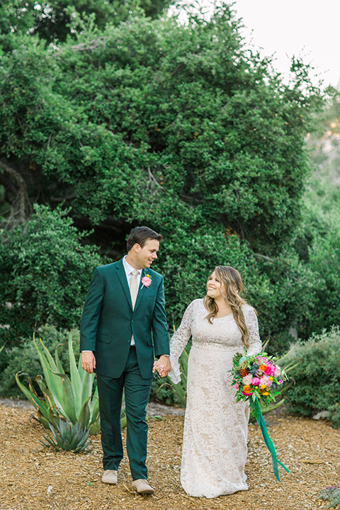 Topa-Winery-Wedding-couple-walking-bride-in-a-bohemian-gown-with-lace-detailing-and-flutter-sleeves-groom-in-a-green-suit-with-a-tan-tie-and-shoes