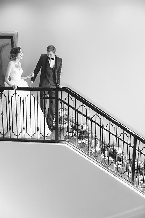 Vellano-Country-Club-black-and-white-photo-of-couple-on-stairs-bride-in-a-big-ballgown-with-her-hair-up-in-a-side-bun-groom-in-a-grey-tuxedo