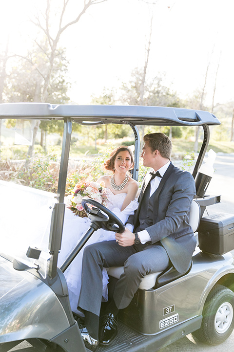 Vellano-Country-Club-bride-and-groom-in-golf-cart-bride-in-a-big-ballgown-with-her-hair-up-in-a-side-bun-groom-in-a-grey-tuxedo