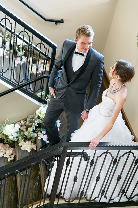 Vellano-Country-Club-bride-and-groom-walking-down-stairs-bride-in-a-big-strapless-ballgown-groom-in-a-grey-tuxedo-with-black-bow-tie