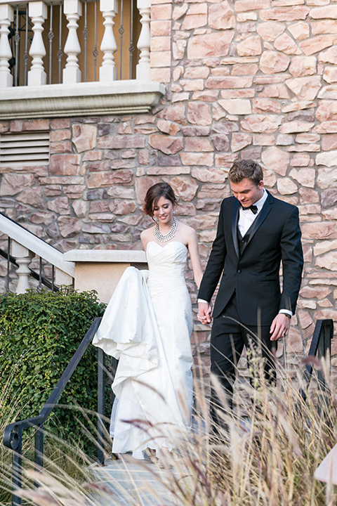 Vellano-Country-Club-bride-and-groom-walking-down-steps-outside-bride-in-a-big-strapless-ballgown-groom-in-a-grey-tuxedo-with-black-bow-tie