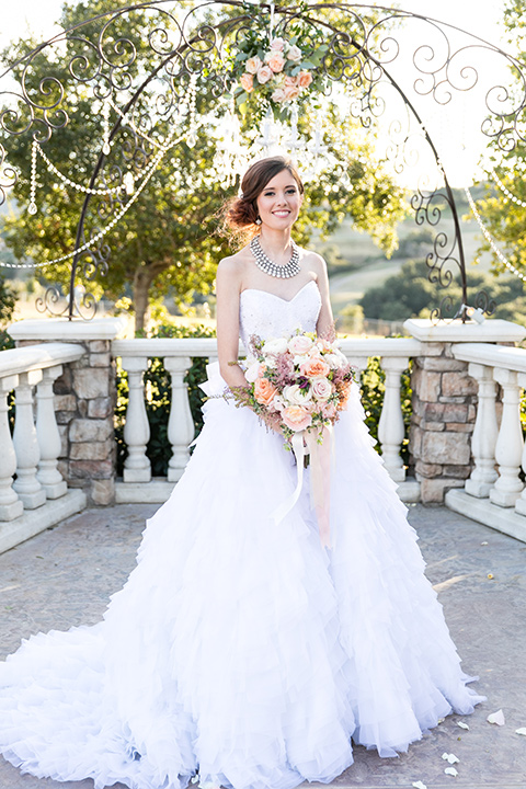 Vellano-Country-Club-bride-standing-holiding-flowers-in-a-big-strapless-ballgown