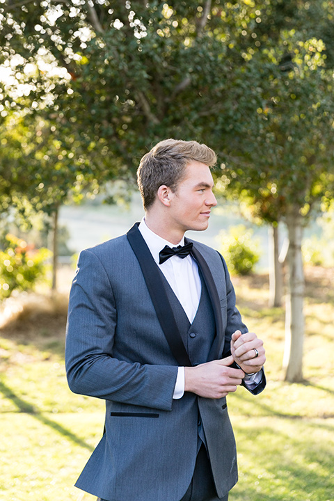 Vellano-Country-Club-groom-fixing-sleeve-in-a-grey-tuxedo