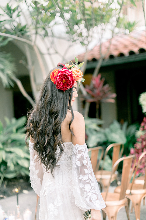 bridal gown from behind the bride is in a bohemian gown with long sleeves and off the shoulder detail her hair is in a long wave with a floral crown