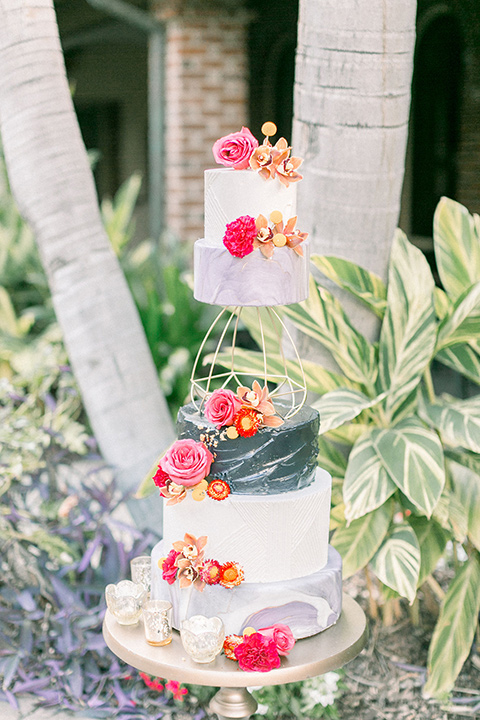 wedding cake in three tiers decorated with pink and gold flowers