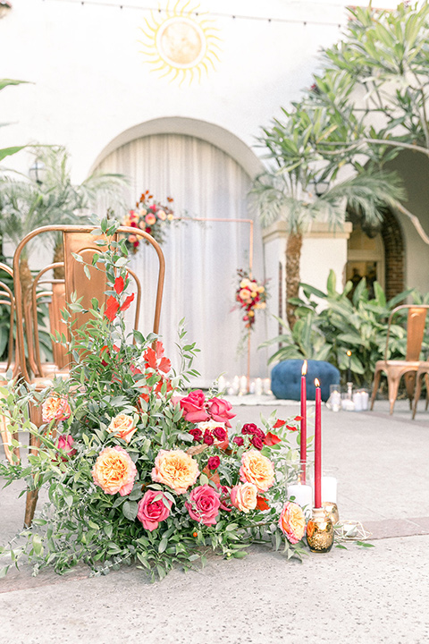 Villa Del Sol ceremony décor with gold metal décor and colorful pink and orange flowers