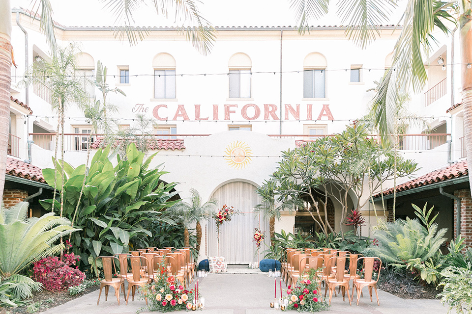 Villa Del Sol ceremony space with bright tropical flowers and gold metal chairs