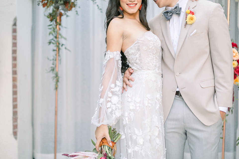 close up on bride and groom attire, the bride is in a bohemian gown with off the shoulder detail with long sleeves the groom is in a tan coat with light grey pants and a grey velvet bow tie
