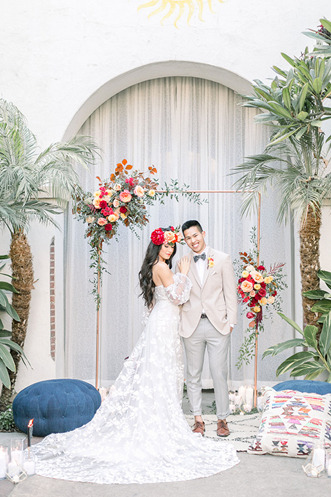 Villa Del Sol couple at the ceremony space the bride is wearing a boho style gown with off the shoulder detail and long sleeves the groom is in a tan suit coat with grey pants and a grey velvet bow tie