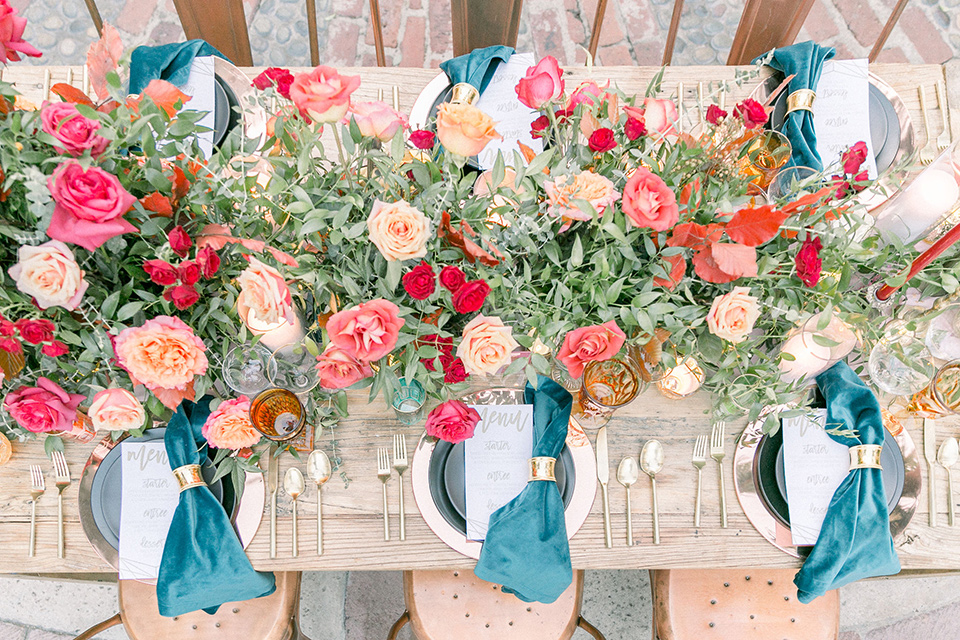 wedding table decor from above with blue napkins and bright colored florals