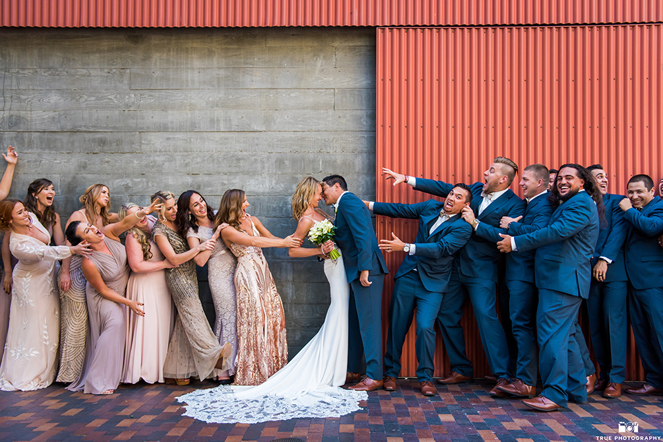 bride and groom being pulled in different directions by groomsmen and bridesmaids