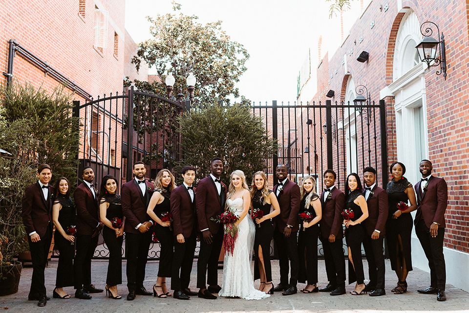 bridal party image with the groomsmen in burgundy tuxedos and bridesmaids in black dresses