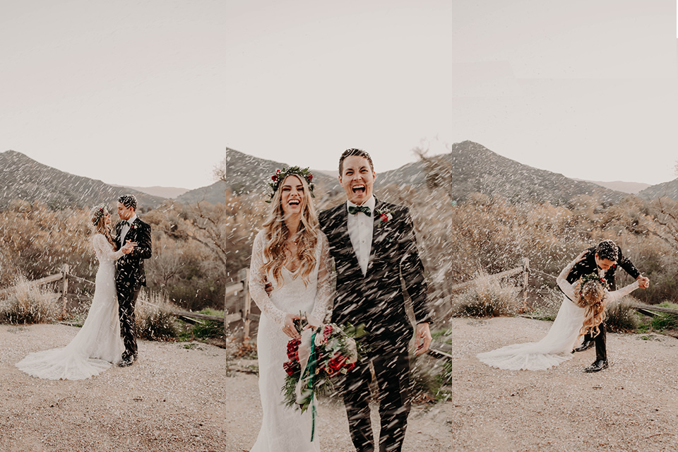 bride and groom in snow, the groom in a black suit with a  green velvet bow tie and the bride in a long sleeved lace gown and a boho floral headpiece
