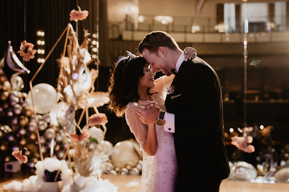 The-Yost-Theatre-bride-and-groom-dancing-bride-in-a-silk-modern-gown-with-star-accessories-and-groom-in-a-velvet-black-tuxedo