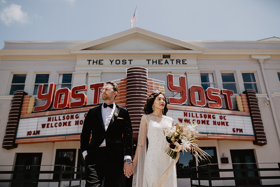 The-Yost-Theatre-bride-and-groom-outside-venue-looking-away-from-each-other-bride-in-a-silk-modern-gown-with-star-accessories-and-groom-in-a-velvet-black-tuxedo