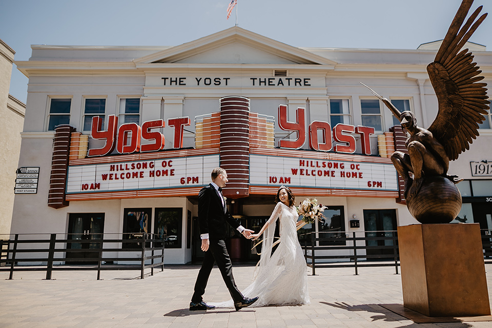 The-Yost-Theatre-bride-and-groom-walking-past-venue-bride-in-a-silk-modern-gown-with-star-accessories-and-groom-in-a-velvet-black-tuxedo