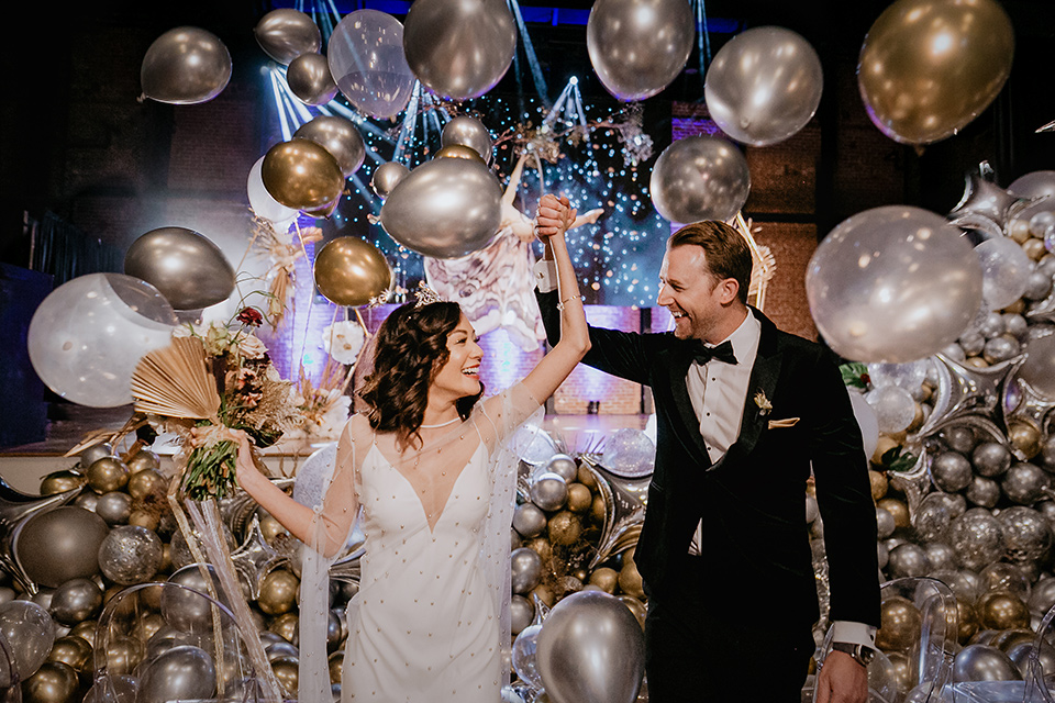 The-Yost-Theatre-bride-and-groom-with-balloons-bride-in-a-silk-modern-gown-with-star-accessories-and-groom-in-a-velvet-black-tuxedo