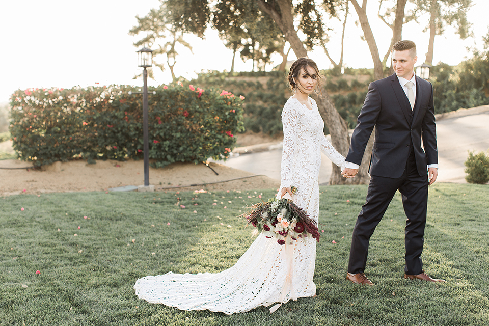 Temecula-outdoor-wedding-at-callaway-winery-bride-and-groom-holding-hands-and-walking-bride-wearing-a-lace-boho-lace-dress-with-sleeves-and-the-groom-in-a-navy-suit-with-champagne-long-tie