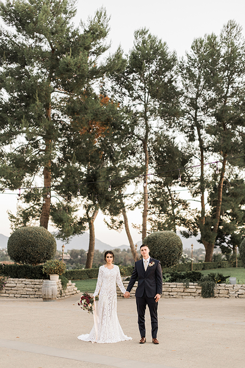 Temecula-outdoor-wedding-at-callaway-winery-bride-and-groom-holding-hands-far-away-with-the-bride-in-a-lace-gown-and-groom-in-a-dark-blue-notch-lapel-suit