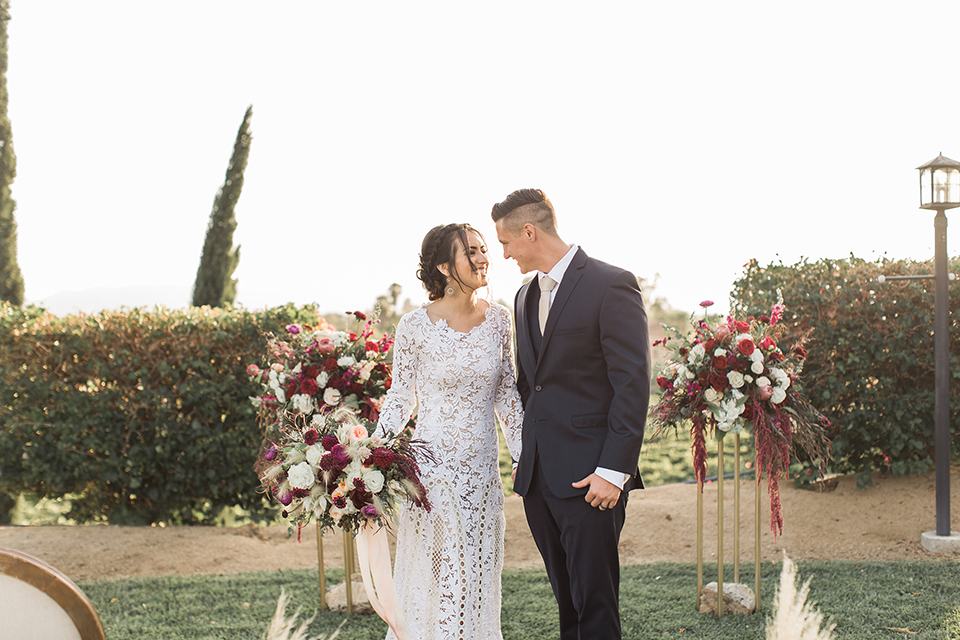Temecula-outdoor-wedding-at-callaway-winery-bride-and-groom-holding-hands-bride-ina-boho-lace-dress-with-sleeves-and-the-groom-in-a-navy-suit