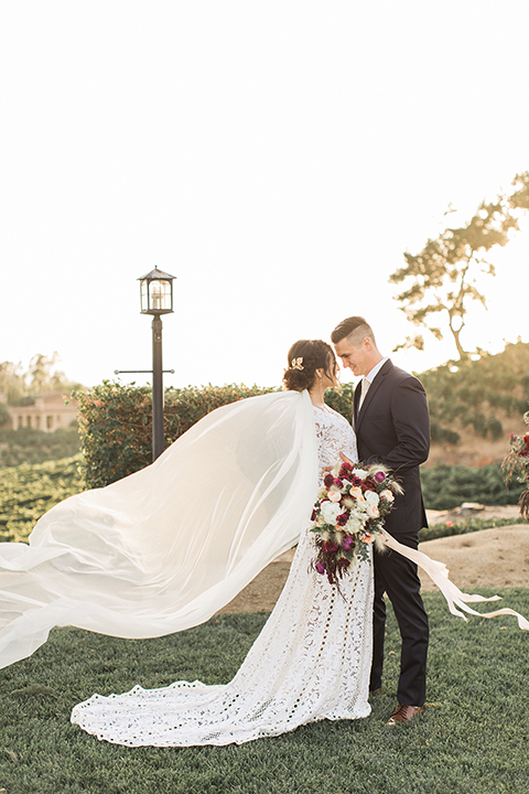 Temecula-outdoor-wedding-at-callaway-winery-bride-and-groom-hugging-and-smiling-bride-in-a-lace-gown-and-groom-in-a-black-notch-lapel-suit