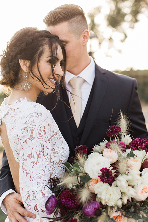 Temecula-outdoor-wedding-at-callaway-winery-bride-and-groom-hugging-close-up-bride-in-a-lace-gown-and-groom-in-a-navy-notch-lapel-suit