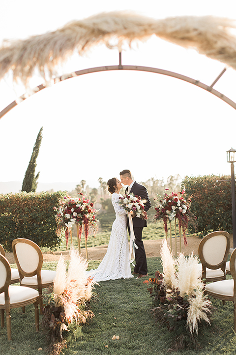 Temecula-outdoor-wedding-at-callaway-winery-ceremony-bride-and-groom-standing-kissing-bride-in-a-lace-dress-with-sleeves-groom-in-a-dark-blue-notch-lapel-suit