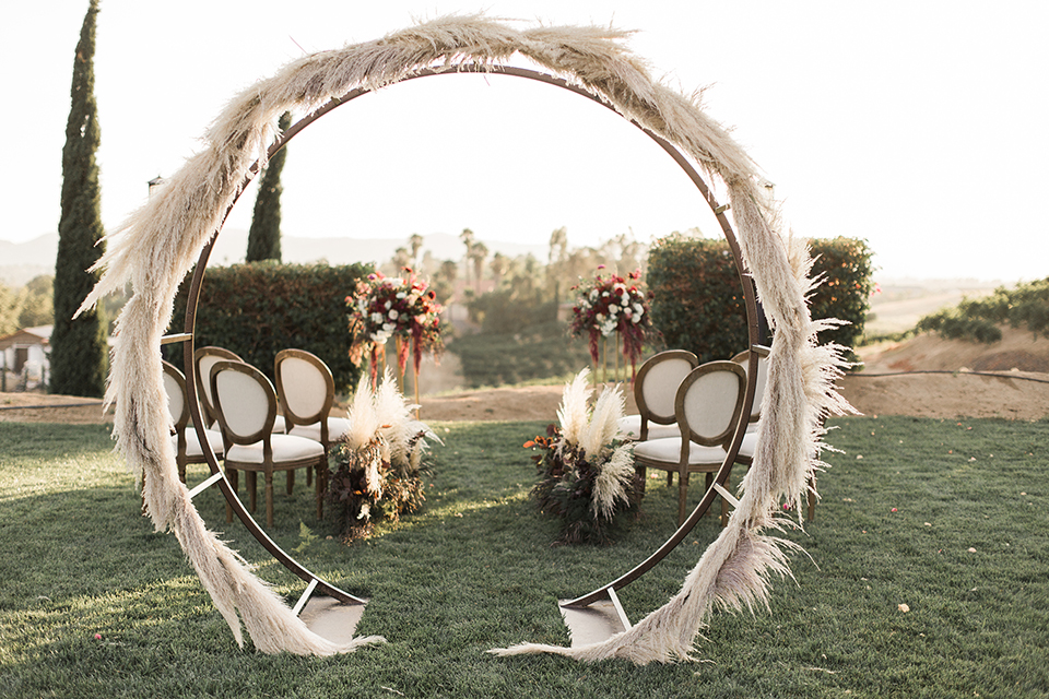 Temecula-outdoor-wedding-at-callaway-winery-ceremony-set-up-feather-grass-bohemian-style-archway