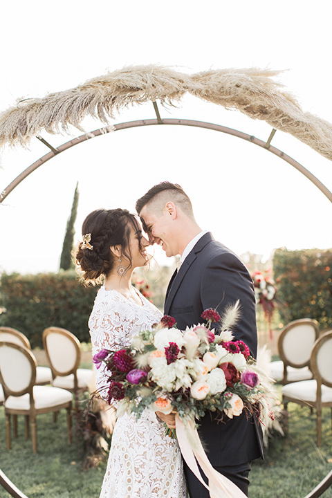 Temecula-outdoor-wedding-at-callaway-winery-ceremony-bride-and-groom-standing-bride-in-a-lace-bohemian-dress-groom-in-a-navy-suit
