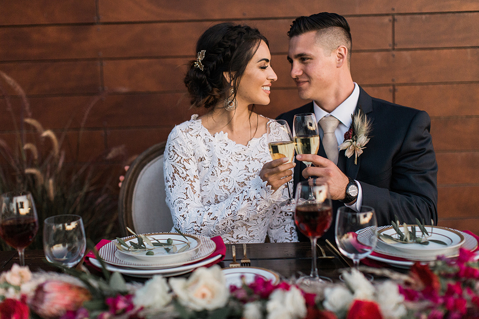 Temecula-outdoor-wedding-at-callaway-winery-table-set-up-sweetheart-table-bride-and-groom-close-up-sitting-with-the-bride-in-a-lace-gown-with-a-high-neckline-and-lace-sleeves-groom-in-a-navy-suit-with-champagne-long-tie