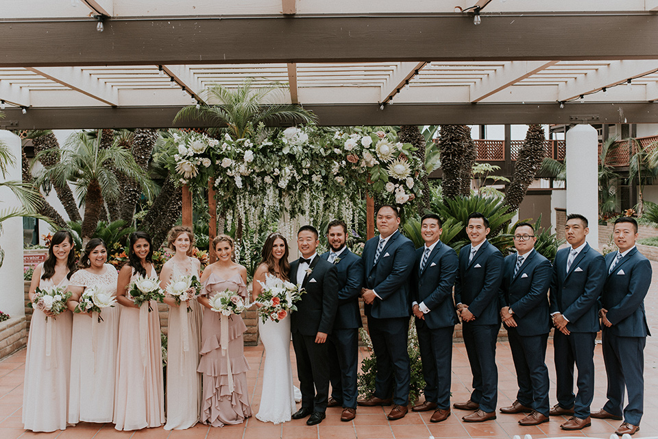 la-jola-shores-hotel-wedding-bridal-party-in-a-line-bridesmaids-in-pink-dresses-groomsmen-in-dark-blue-suits-bride-in-a-formfitting-satin-dress-with-straps-groom-in-a-navy-tuxedo-with-black-shawl-lapel