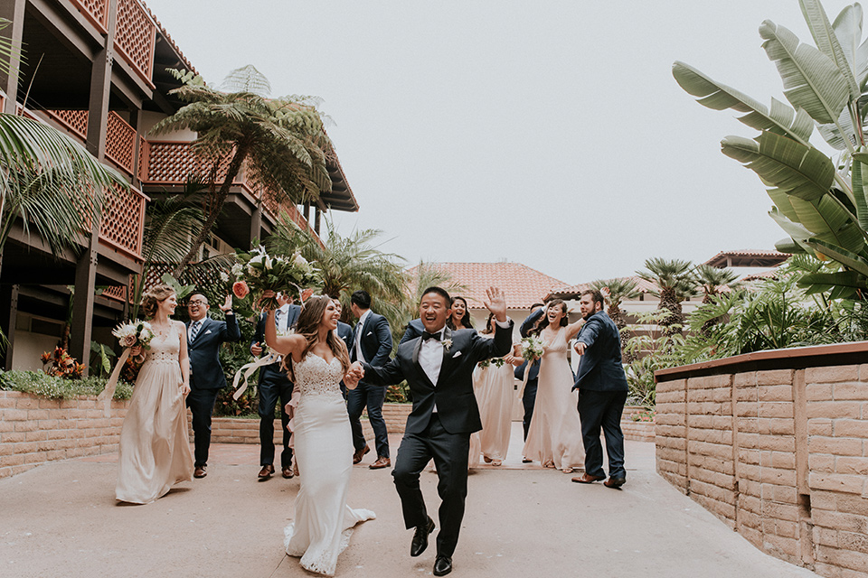 la-jola-shores-hotel-wedding-bridal-party-walking-bridesmaids-in-pink-dresses-groomsmen-in-dark-blue-suits-bride-in-a-formfitting-satin-dress-with-straps-groom-in-a-navy-tuxedo-with-black-shawl-lapel