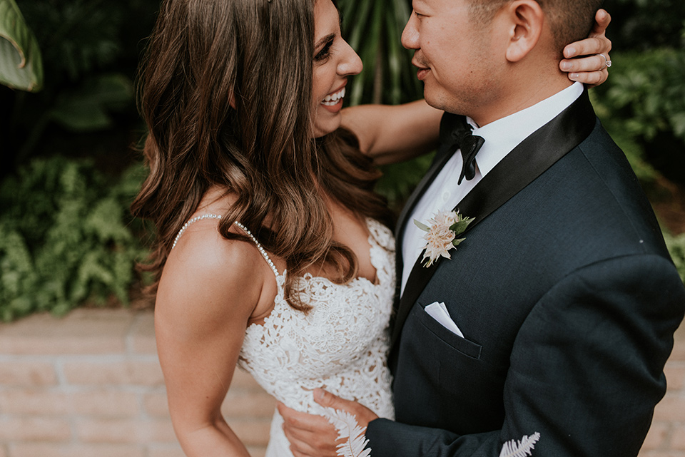la-jola-shores-hotel-wedding-close-up-on-bride-and-groom-bride-in-a-formfitting-satin-dress-with-straps-groom-in-a-navy-tuxedo-with-black-shawl-lapel