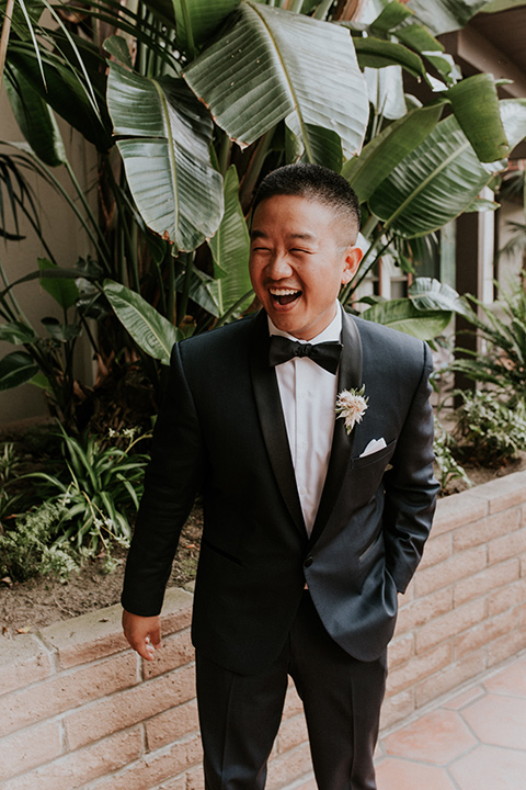 la-jola-shores-hotel-wedding-groom-laughing-in-a-navy-shawl-lapel-tuxedo-and-black-bow-tie