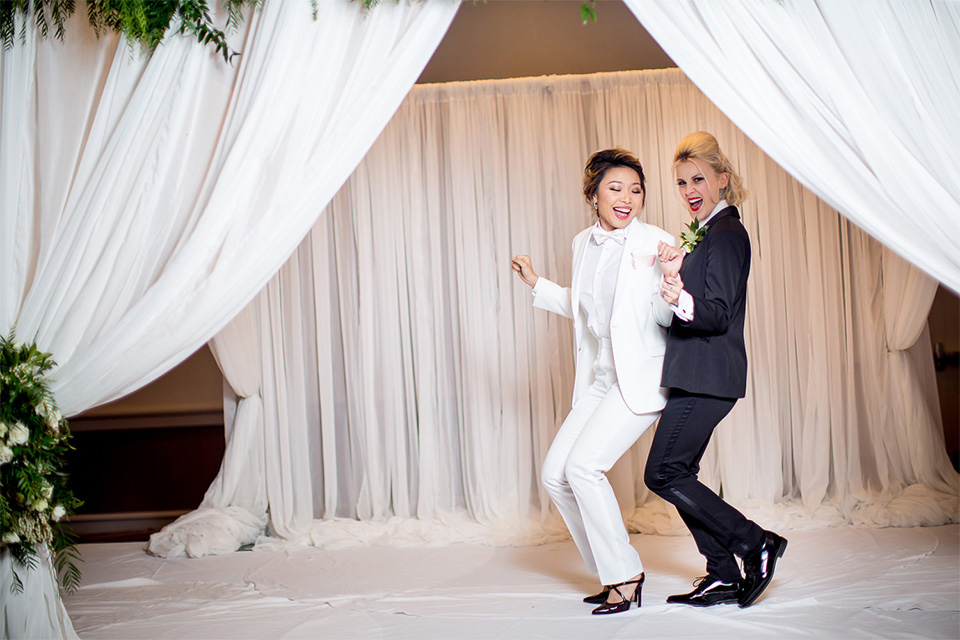 two-brides-dancing-one-in-a-white-tuxedo-and-one-in-a-black-tuedo