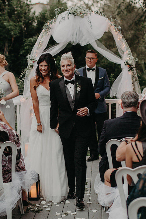two-brides-at-their-ceremony-one-bride-in-a-flowing-white-gown-the-other-in-a-black-tuxedo-with-a-grey-vest-and-black-bowtie