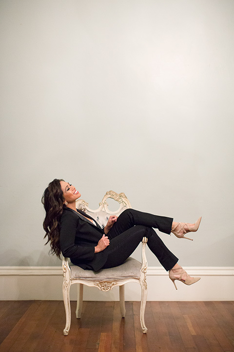 female-tuxedo-sitting-in-a-chair-in-a-shawl-lapel-black-tuxedo-and-nude-high-heels